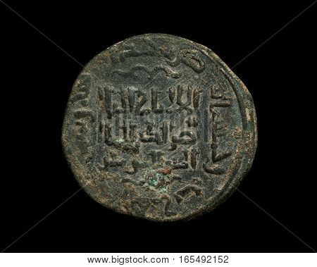 Ancient Islamic Copper Coin With Text On It Isolated On Black
