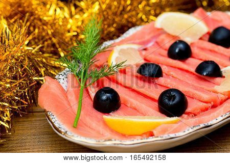 sliced red fish salmon greens lemon black olives on plate, wooden brown background, top view, holiday food serving