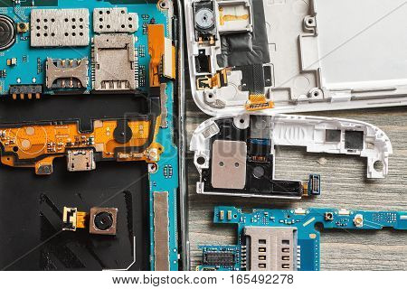 Parts Of Disassembled Digital Gadgets On Wooden Table