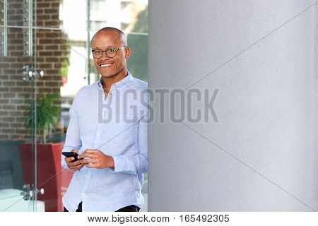 African Businessman Standing With Mobile Phone
