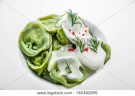 Ravioli pasta from green dough with mushroom stuffing, oil, parsley, vegetarian dish