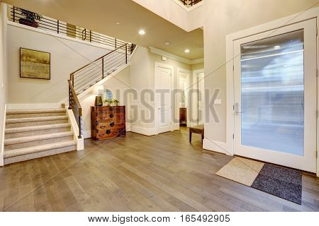 Light modern foyer design boasts vintage steamer trunk dresser next to staircase with metal horizontal railings glossy entrance door and dark hardwood floors. Northwest USA poster