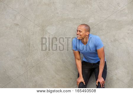Handsome African Man Smiling With Hands On Knees