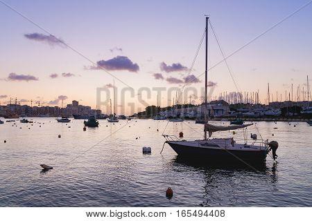 Sunset at Marsamxett harbour. Many sailing yachts lie alongside. Valletta Malta.