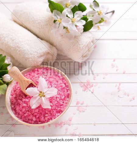 Spa or wellness setting. Pink sea salt in bowl towels and flowers on white wooden background. Selective focus. Place for text. Square image.