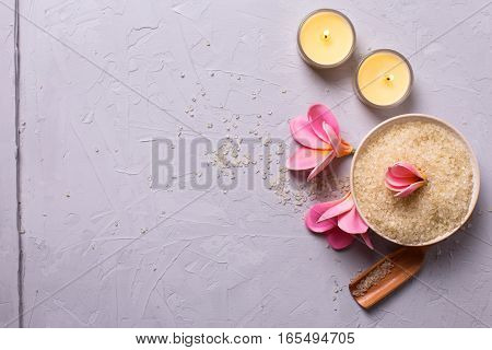 Spa or wellness setting in yellow color. Sea salt in bowl candles and flowers on grey textured background. Selective focus. Place for text.