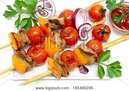 skewers of meat with vegetables and herbs on a white background. horizontal photo.