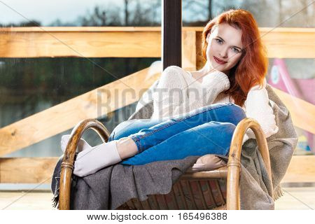 Atractive Red-haired Woman Resting Sitting On Rocking Chair In Front Of Window