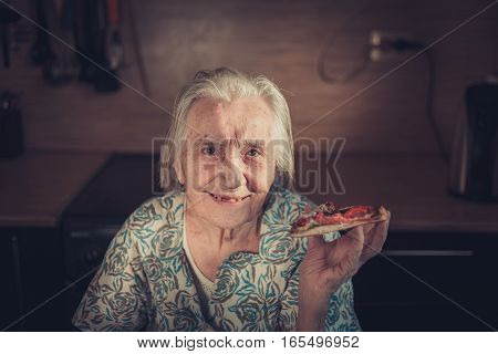 Very Elderly Woman Eating A Piece Of Pizza At Home.