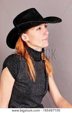 Portrait of red-haired woman in a hat on a gray background.