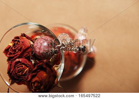 Still-life with an elegant glass, petals, dried roses and jewelery
