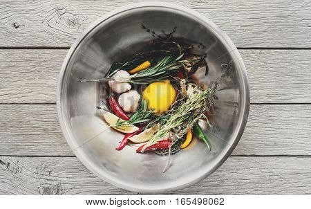 Cooking background. Lemon, herbs, chili, garlic and other seasoning ingredients in metal bowl on rustic wood, top view. Vegetables and herbs ready for making steak marinade
