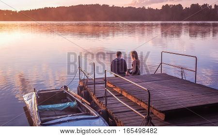 Romantic couple sitting on the pier golden sunset. Beautiful nature on the lake. A man and a woman meet sunset. Beautiful couple outdoors near water