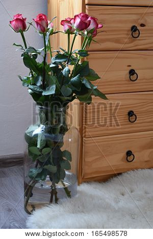 Seven bouquets of roses in a vase built with wooden dressers. Rose.