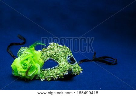 Theatrical mask with a flower against a dark background