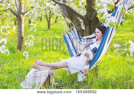 Beautiful pregnant woman sitting in hammock in blooming garden. Lazy time