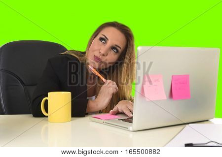 attractive 40s blond business woman working at office laptop computer sitting on the desk absent minded and thoughtful smiling happy as if thinking of vacation isolated green chroma key screen