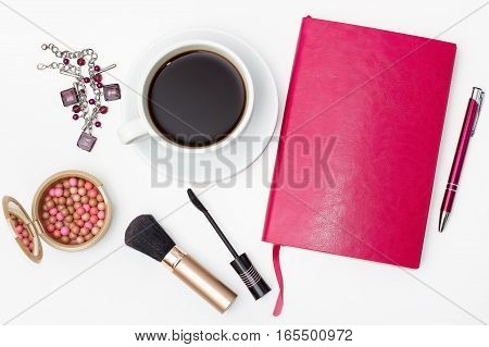 flat lay Cup of black coffee jewelry diary with pen brush for makeup and other accessories on a white background.