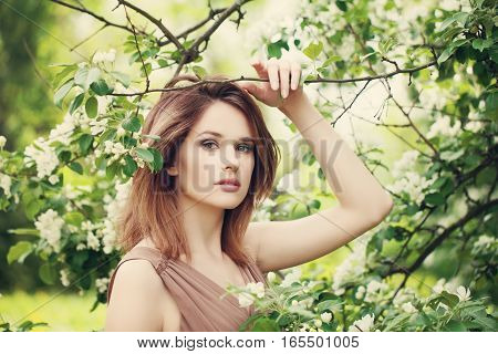 Fashion Beauty Portrait of Beautiful Model Woman in Spring Sunny Park. Pretty Woman on Flowers Background