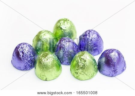 a few chocolates in green and purple packaging on white.
