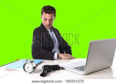 young attractive businessman at office computer desk posing with gun and alarm clock in deadline pressure and timing projects concept isolated on green chroma key screen background