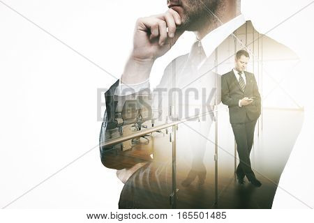 Thoughtful man using smartphone in modern office. Communication concept. Double exposure
