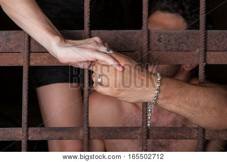Man and woman hold hands through bars concept of fidelity
