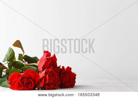 Bunch of red roses on white table