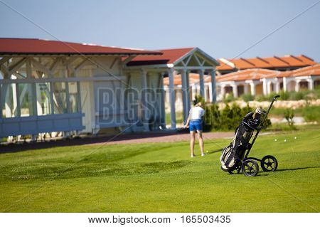golf bag with woman playing on the background