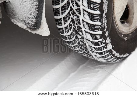 Close up of car tyre in winter covered with snow. Winter tyre in extreme cold temperature