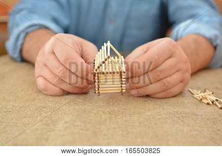 Old Man Engaged In Manual Work Glue House With Matches. Building Dreams. Handmade. Free Place. Needl