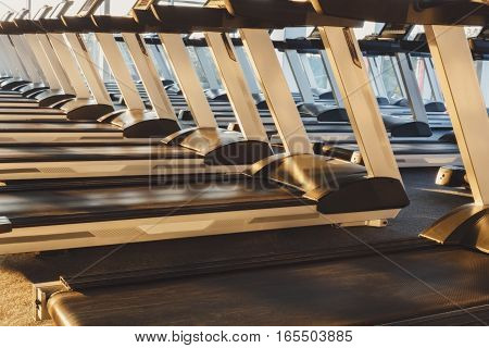 Modern gym interior with equipment. Fitness club with row of treadmills running part closeup for fitness cardio training in evening backlight. Healthy lifestyle concept