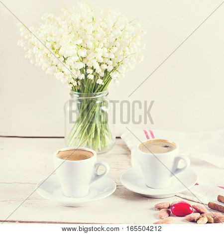 Two cups of coffee - espresso heart and bouquet of flowers - lilies of the valley on white background. romantic breakfast for my birthday Valentine's Day.