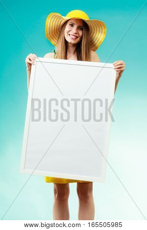 Holidays summer and advertisement concept. Woman wearing yellow hat and bikini holding blank presentation board. Female model posing on blue background.
