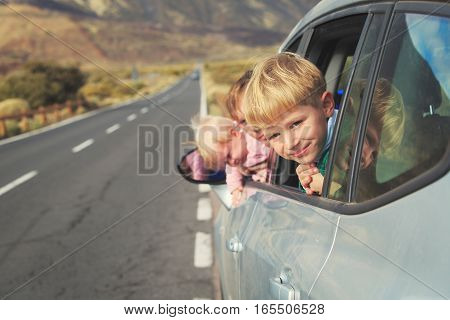 family travel by car- happy father with kids driving car on road in mountains