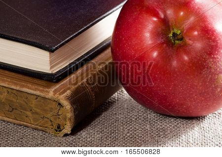 Detail Of Old Books In Hardcover And Close-up Red Apple