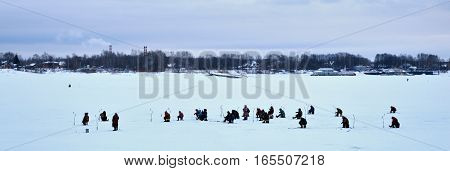 Winter landscape picture frozen river Volga in Yaroslavl, Russia, many fishermen are engaged in ice-fishing in the bitter cold