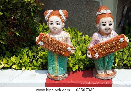 Two Thai girls ceramic figurines holding welcome sign in English and Thai. Smiling women statuettes wearing traditional clothes with signboards inviting guests to the hotel. Colorful greeting sculpture at the entrance door