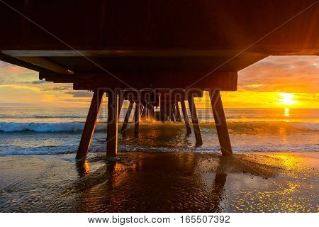 Dramatic sunset view from under Glenelg jetty South Australia