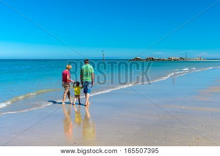Grandfather and grandmother with grandson dreaming and holding hands of each other on the beach.