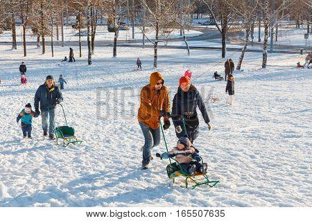 GRODNO BELARUS - DEC 04: Families enjoy sledding on a snowy hill in a city Park at December 04 2016 in Grodno Belarus