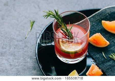 Red Drink in Glass with Rosemary and Lime