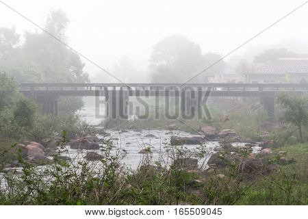 Morning mist lingering over concrete bridge. Nan province Thailand.