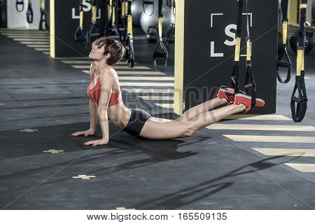Pretty smiling girl with closed eyes stands on the hands on the floor in the gym. Her feet are on the TRX straps. She wears red top and sneakers, black shorts. Shoot from the side. Horizontal.