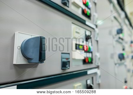 Closeup of lit lights and control dials on manufacturing machinery in power plant or refinery plant