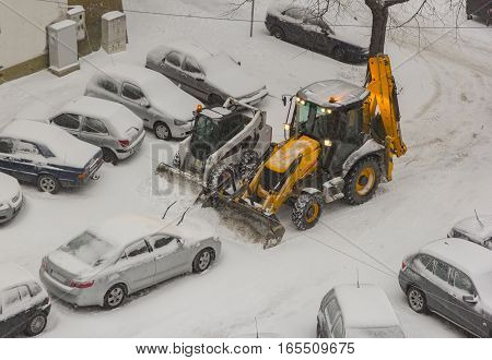 two excavators cleaning snow on car parking. Top view.