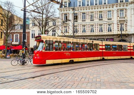 Hague, Netherlands - April 5, 2016: Red tram and dutch traditional houses on background in Den Haag, Holland