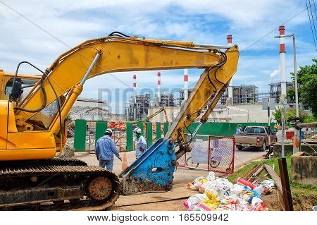 Yellow excavator against  construction site or demolition site of power plant with clear sky