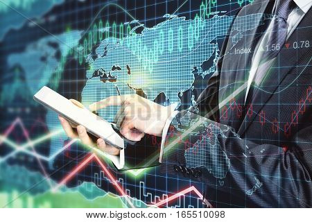 Close up of businessman using tablet on forex chart background. Trading concept