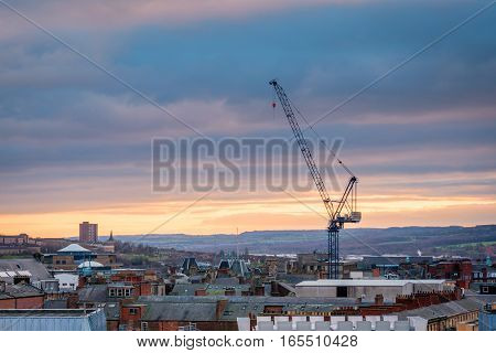 Tall Crane in Newcastle Skyline, in the city centre, towers above the rooftops as the sun sets